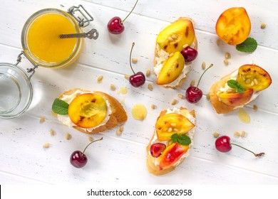 Homemade fresh sweet toasted toast with fruit. Peach and cherry sandwiches with nuts and honey on a white wooden table. Healthy snack. Top view.