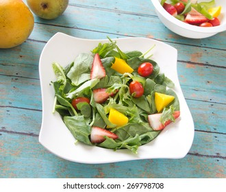 Homemade fresh vegan salad with chopped vegetables, fruits, spring greens and spinach. Arranged on a painted wooden table with side of fruits