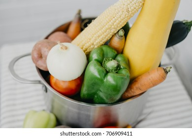 Homemade fresh vegetables in a metal saucepan on a table on a white background