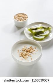 Homemade fresh yogurt in a white cup with kiwi and oat flake.