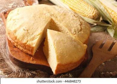 Homemade fresh-baked corn bread close-up on a wooden board. Horizontal