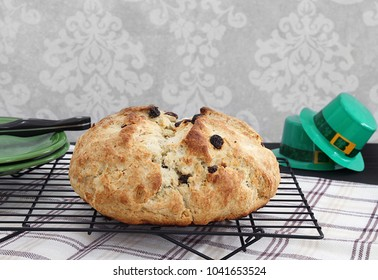 Homemade, freshly baked Irish Soda Bread on a cooling rack.  Irish decorations to the side.  Great for St. Patrick's Day celebration.