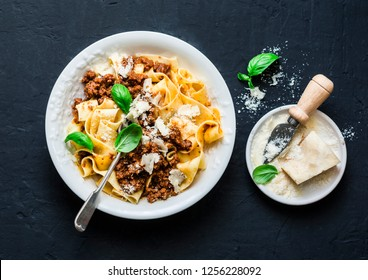 Homemade freshness pappardelle pasta with beef bolognese sauce on a dark background. Traditional Italian  pasta