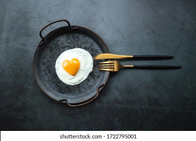 Homemade fried egg in a vintage pan and stylish cutlery on a dark background. Heart-shaped yolk.View from above. Copy space for text.