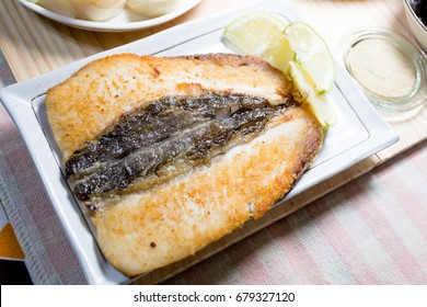 Homemade fried milkfish with sliced lemon and pepper salt.