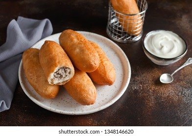 Homemade fried pies with liver and potatoes. Food on a dark background