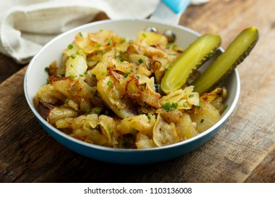 Homemade fried potato with pickled cucumber