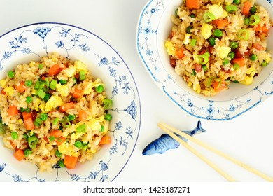 Homemade fried rice with bacon, peas, egg, carrot and scallions in pretty blue and white bowls with chopstics on ceramic fish rest.