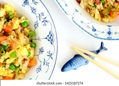 Homemade fried rice with bacon, peas, egg, carrot and scallions in pretty blue and white bowls with chopsticks on ceramic fish rest.