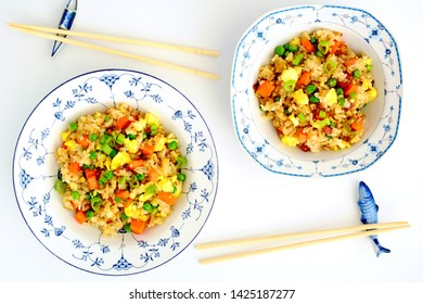 Homemade fried rice with bacon, peas, egg, carrot and scallions in pretty blue and white bowls with chopsticks on ceramic rests.