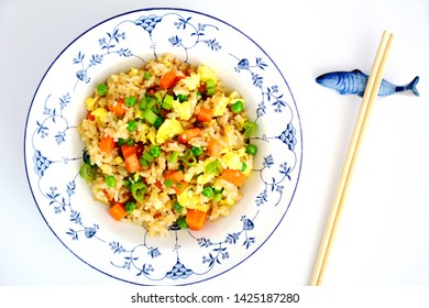 Homemade fried rice with bacon, peas, egg, carrot and scallions in pretty blue and white bowl with chopsticks on ceramic fish rest.