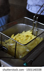 Homemade fries from fresh potatoes lie in a fryer and are roasted golden yellow - delicious fresh chips directly from Germany