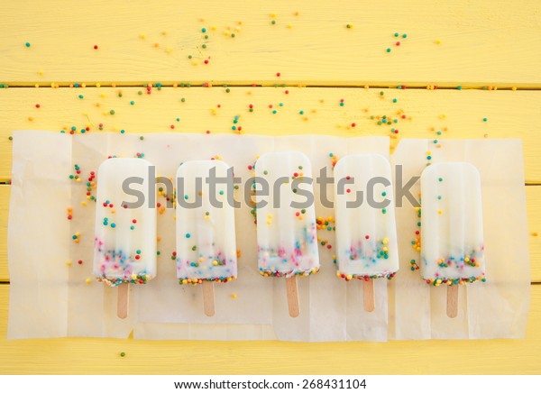 Homemade frozen vanilla popsicles with colorful sprinkles