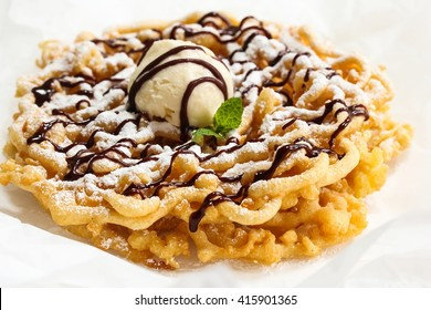 Homemade Funnel cake  topped with ice cream powdered sugar and chocolate drizzle isolated on white, selective focus