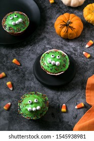 Homemade funny monster cupcakes with green sugar icing. Delicious bakery sweets for the celebration of Halloween. Selective focus.