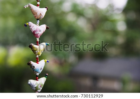 A homemade garland decoration made of sewn hearts and beads hangs against a lush outdoor background.