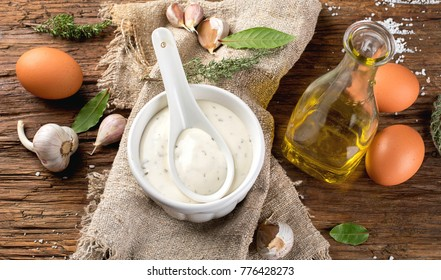 Homemade Garlic mayonnaise sauce on rustic wooden background. Aioli dip.