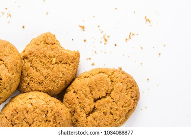 Homemade ginger biscuit with peanuts and raisins. Delicious honey sweetmeal digestive cookie on a plate. On a white background with light shadow. Detailed closeup studio shot with selective focus.