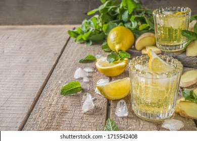 Homemade ginger lemonade cocktail. Cold summer ginger lemon ale. Sweet and sour iced refreshing beverage with lemon slice garnish,  Detox and weight loss drink. Wooden rustic background copy space