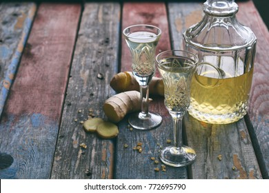 Homemade ginger tincture or ale on wooden background. Rustic style. Spice yellow liqueur in a glass. Alcohol drink.