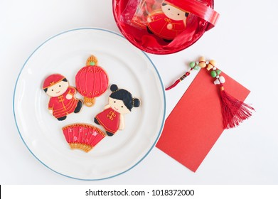 Homemade gingerbread as Chinese boy and girl dolls in the white plate and red envelopes for Chinese New Year on thw white blackground.
