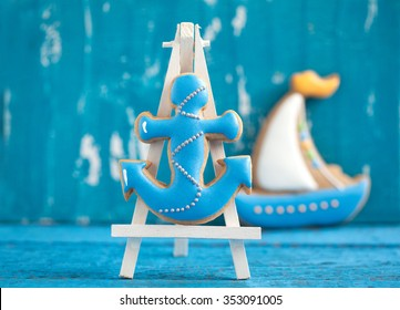Homemade homemade gingerbread cookie in the shape of boat and anchor on a blue wooden background. Space for text and selective focus.