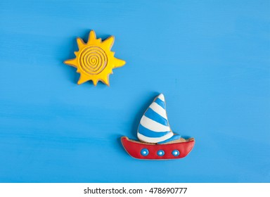 Homemade homemade gingerbread cookie in the shape of boat and the sun on a blue wooden background. Space for text and selective focus.