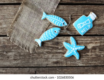 Homemade homemade gingerbread cookies in the form of two fish, a bottle with a note and a starfish on the wooden table. Space for text and selective focus.