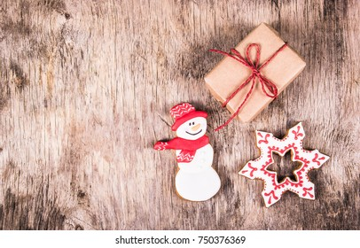 Homemade gingerbread cookies and gift box. Wooden texture. New Year's and Christmas.