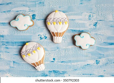 Homemade gingerbread cookies in the shape of air balloons and clouds on a blue table. Space for text and selective focus.