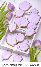 Homemade gingerbread cookies in the shape of purple tulip on wooden table