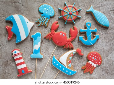 Homemade homemade gingerbread cookies in the shape of steering wheel, lighthouse, ship, fish and anchor on a wooden background
