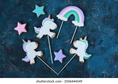 Homemade gingerbread cookies in the shape of unicorns, stars, rainbow on a wooden background