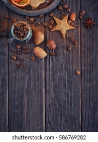 Homemade gingerbread cookies, spices and decorations on wooden background. Seasonal holidays concept.
