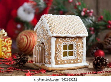 Homemade gingerbread house with candy windows on a wooden table with Christmas decorations. Selective focus and space for text.