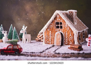 Homemade gingerbread house. Christmas concept. gingerbread house, cookies, tiny car toy with tree and deer with christmas tree at background