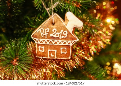 Homemade gingerbread house covered with white icing and letters PF 2019, hanging on cord on Christmas tree, golden yellow chain ornament, fairy lights