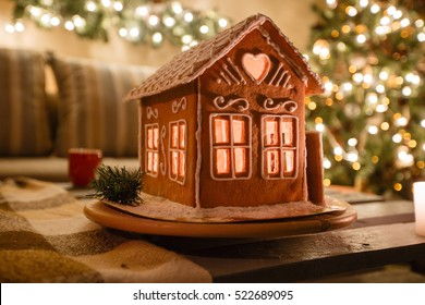 Homemade gingerbread house on background room decorated for Christmas.