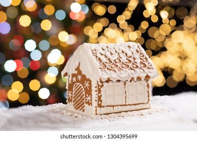 Homemade gingerbread house on bokeh background.