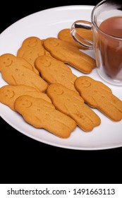 Homemade gingerbread men. Tea and ginger cookie biscuits comfort food served on a white plate against black background. Fun winter childrens home cooking snack.