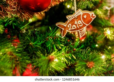 Homemade gingerbread in shape of a fish covered with white icing and letters PF 2019, hanging on cord on Christmas tree, golden yellow chain ornament, red baubles, lights in background, copy space