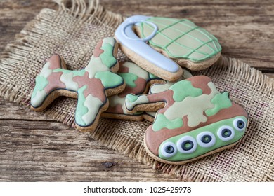 "Homemade Gingerbreads in the form of a grenade, a tank, fighter aircraft and the numbers ""23"" in protective khaki color on Defender of the Fatherland Day"