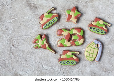 "Homemade Gingerbreads in the form of a grenade, tank, fighter aircraft and the numbers ""23"" in protective khaki color on Defender of the Fatherland Day"