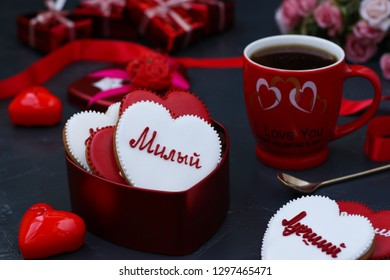 """Homemade gingerbreads in the shape of hearts with the words in Russian """"dear, best, beloved, sweet"""" for Valentine's Day in a box on a dark background"""