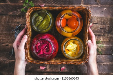 Homemade glass jars of pickled fresh cucumbers, juicy tomatoes, sweet zucchini in a wicker box on a wooden background. Stock of food. Autumn concept. Top view