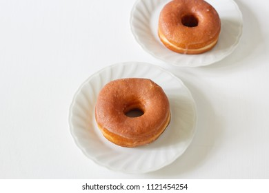homemade glazed donuts in white plate.