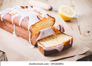 Homemade glazed lemon pound cake on rustic wooden table, sliced and ready to eat