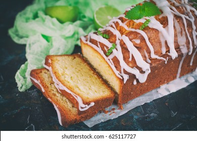 Homemade glazed lime pound cake, decorated with mint, on vintage table, sliced and ready to eat.