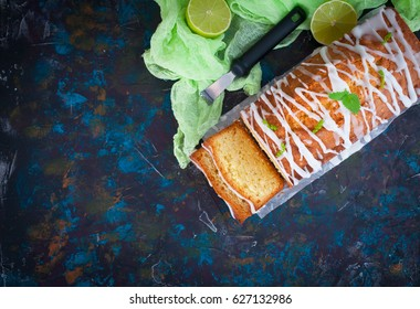 Homemade glazed lime pound cake, decorated with mint, on vintage table, sliced and ready to eat. Space for text