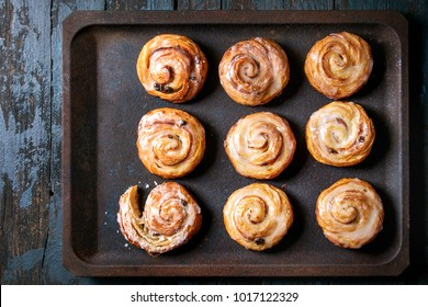 Homemade glazed puff pastry cinnamon rolls with custard and raisins on oven tray over old dark blue wooden background. Top view. Rustic style